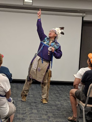 Man in traditional Onondaga dress points to sky as he tells story to audience