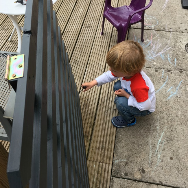 toddler-crouched-by-picket-gate-with-awl-prodding-something