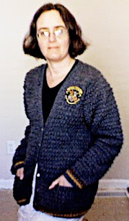 Cynthia M. Parkhill wearing gray, hand-crocheted cardigan. The sleeves and hem are bordered with stripes of yellow and red, and there is a 'Hogwarts' crest appliqued onto the left breast of the sweater