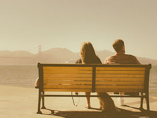couple on bench in front of hills