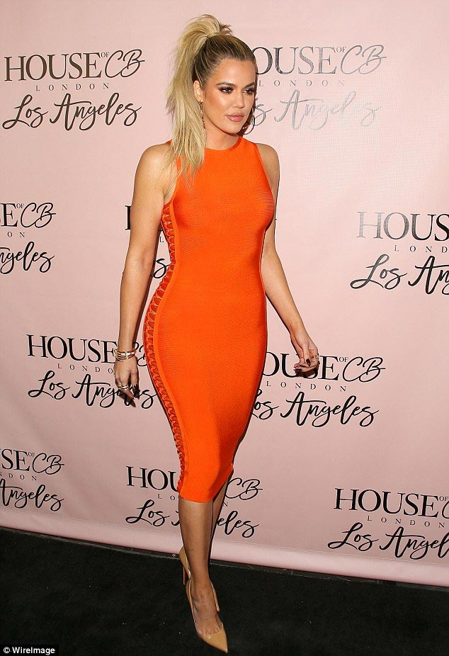 Khloe Kardashian shows off curves in tight orange dress