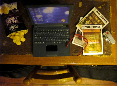 Modern dolls' house miniature desk, from above, showing an opened bag of chips, a laptop, several issues of The tiny Times magazine, red reading glasses and a digital camera.