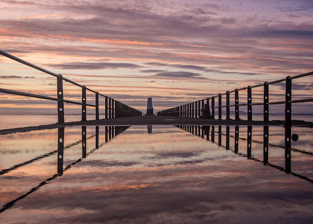 Photo of the sunset reflected in a puddle on Maryport pier