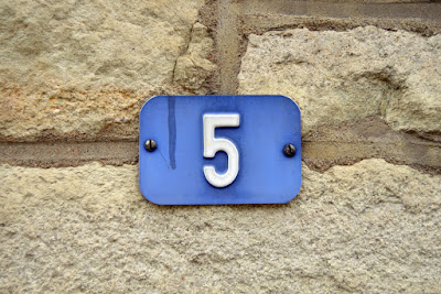 a plaque with the number 5 is attached to a wall
