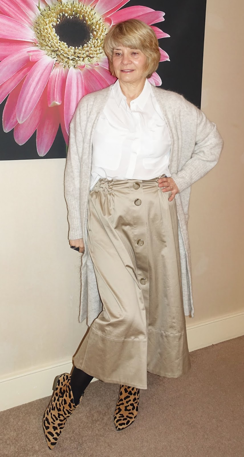 A fawn midi skirt worn with white silk blouse and long ivory cardigan and leopard print boots