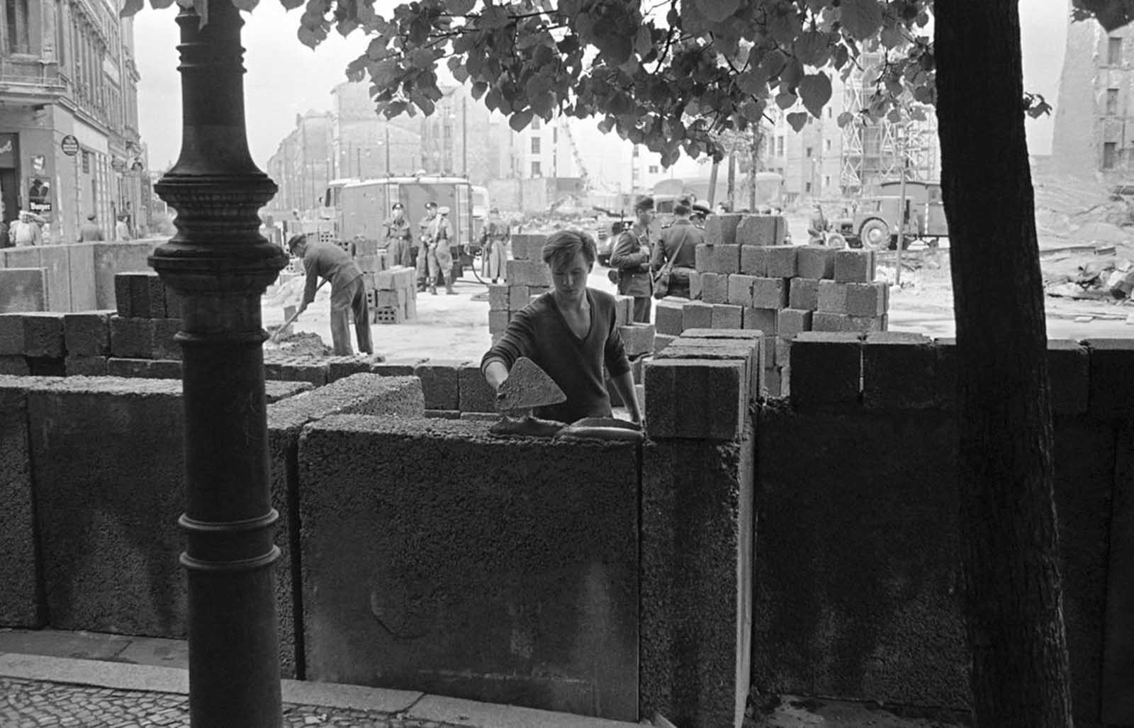 A young East Berliner erects a concrete wall that was later topped by barbed wire at a sector border in the divided city August 18, 1961. East German police stand guard in background as another worker mixed cement.