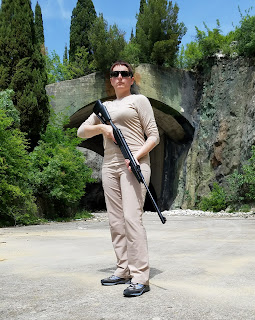 woman with gun in front of bunker