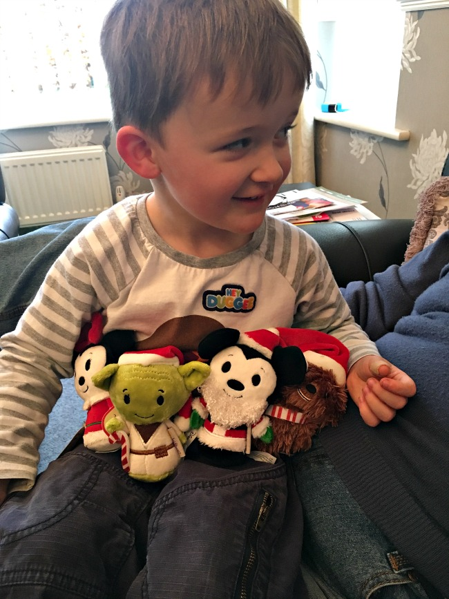 toddler-looking-sideways-with-four-hallmark-itty-bittys-on-his-lap-minnie-mouse-yoda-mickey-mouse-and-chewbacca-all-wearing-Christmas-hats