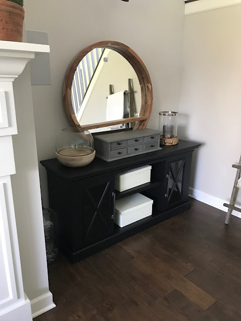 Round mirror above TV console