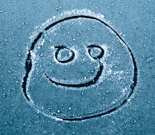 smiley face drawn on frozen windscreen