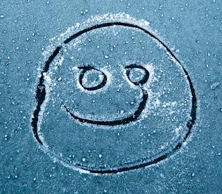 smiley face drawn on frozen windscreen
