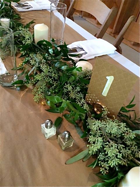 Brown Paper Covering The Tables Is Topped With Garland That Runs Straight Down Center Highlighted Various Candles And Accoutrerments