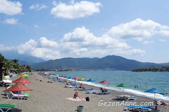 Çalış plajında kumsalda güneşlenenler ve hafif dalgalı denize girenler, arkada Fethiye merkez