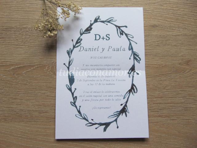 Invitación estilo tarjetón con corona de hojas dibujada en acuarela