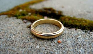 sortija de matrimonio sobre superficie de cemento junto a una grieta llena de musgo