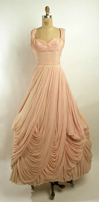 Light peach ballgown with draping and pleating in multiple tiers designed by Jean Dessés displayed on dress form