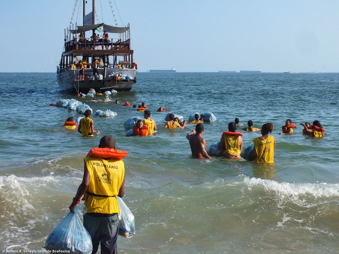 Voluntários carregando a escuna com resíduos coletados durante uma Ação Voluntária EcoFaxina.