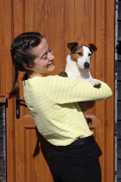 Abbey, wearing a lemon yellow stripe top, holds Buddy, a terrier, over her shoulder