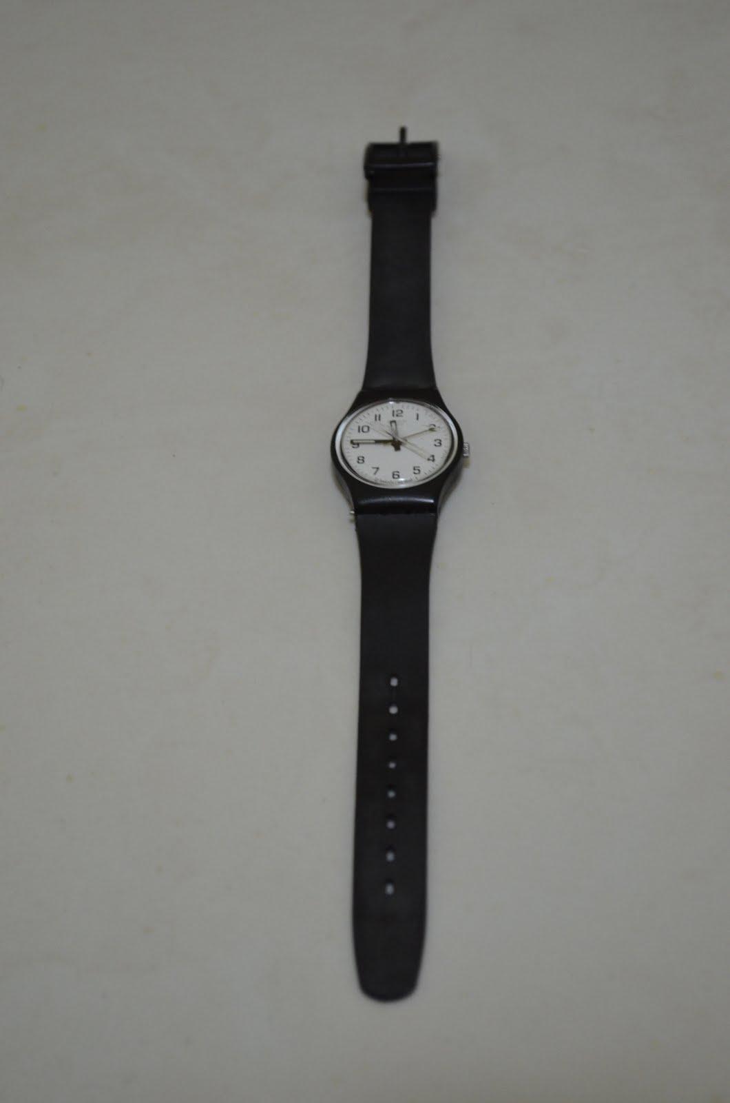 dd1da37a87c Relógio Swatch preto com fundo branco e pulseira de borracha.