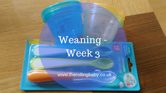 Weaning spoons and weaning tubs sitting on a wooden table