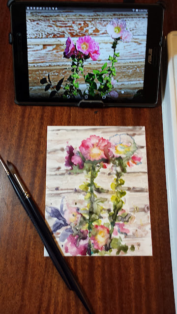 Watercolor painting of hollyhocks on Yupo surface.  Brushes on left.  Tablet in background.