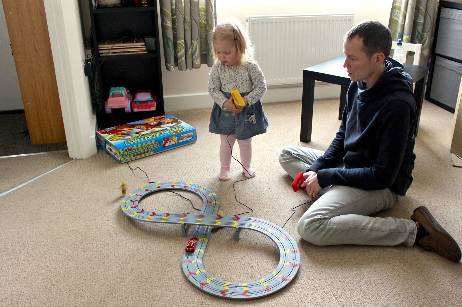 Elise is stood next to the scalextric track. My husband is sitting. They are both holding controllers and racing the cars on the track. Elise has pushed the trigger too much and her car has come off the track.
