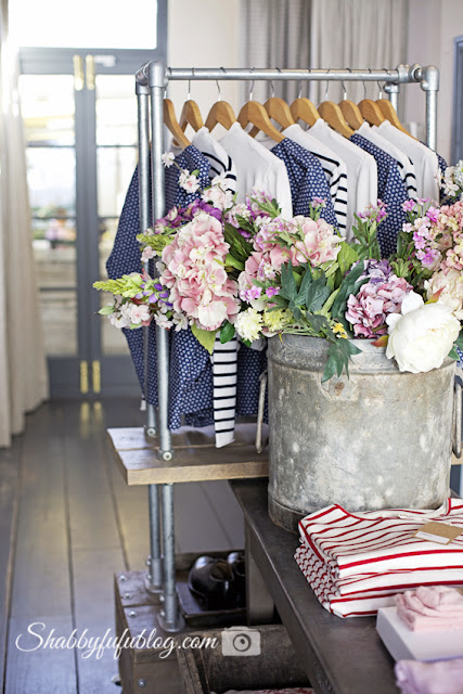 Pink and white flowers brighten up the Cabbages & Roses showroom, along with shabby chic style clothing rack and the bright Chelsea sun.