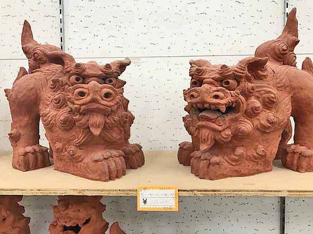 Pair of Shisa statues on wooden shelf