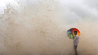 In this Wednesday, June 29 photo, a man holds an umbrella as water engulfs him during high tide on the Arabian Sea coast, in Mumbai, India. (Credit: AP Photo) Click to Enlarge.