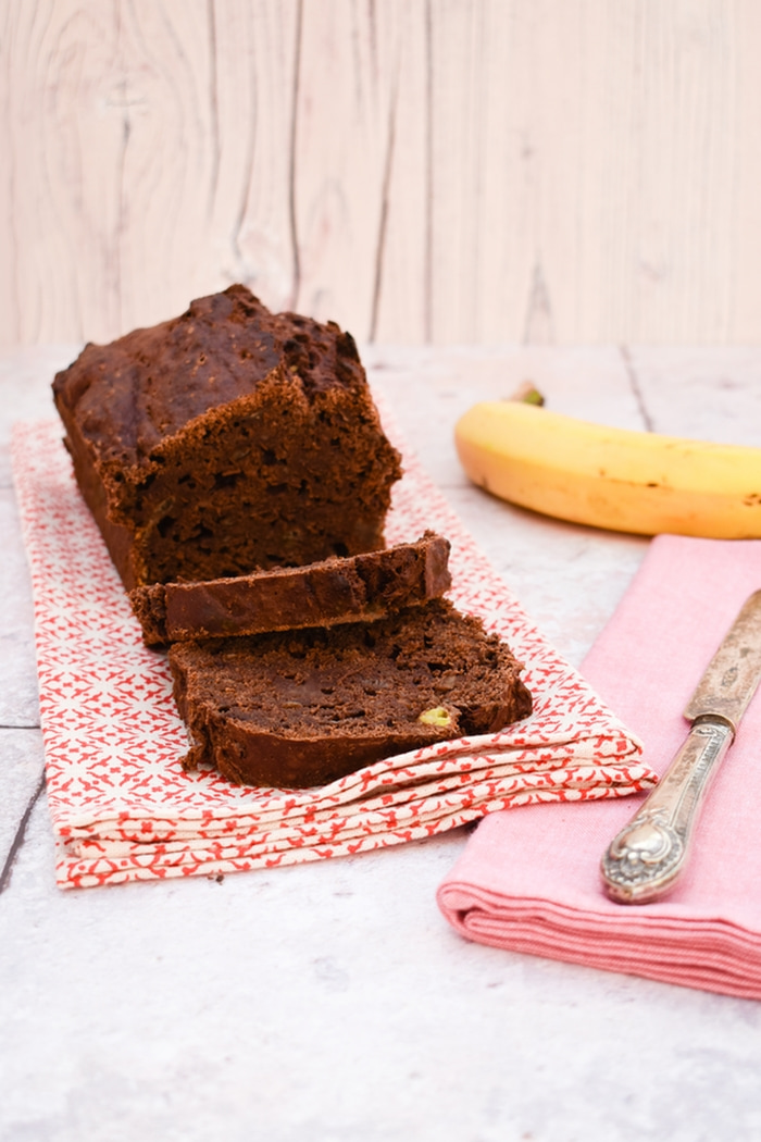 a sliced chocolate banana bread next to a knife on a pink napkin and a banana