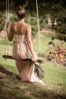 Invitada de boda con vestido color blush sentada en un columpio
