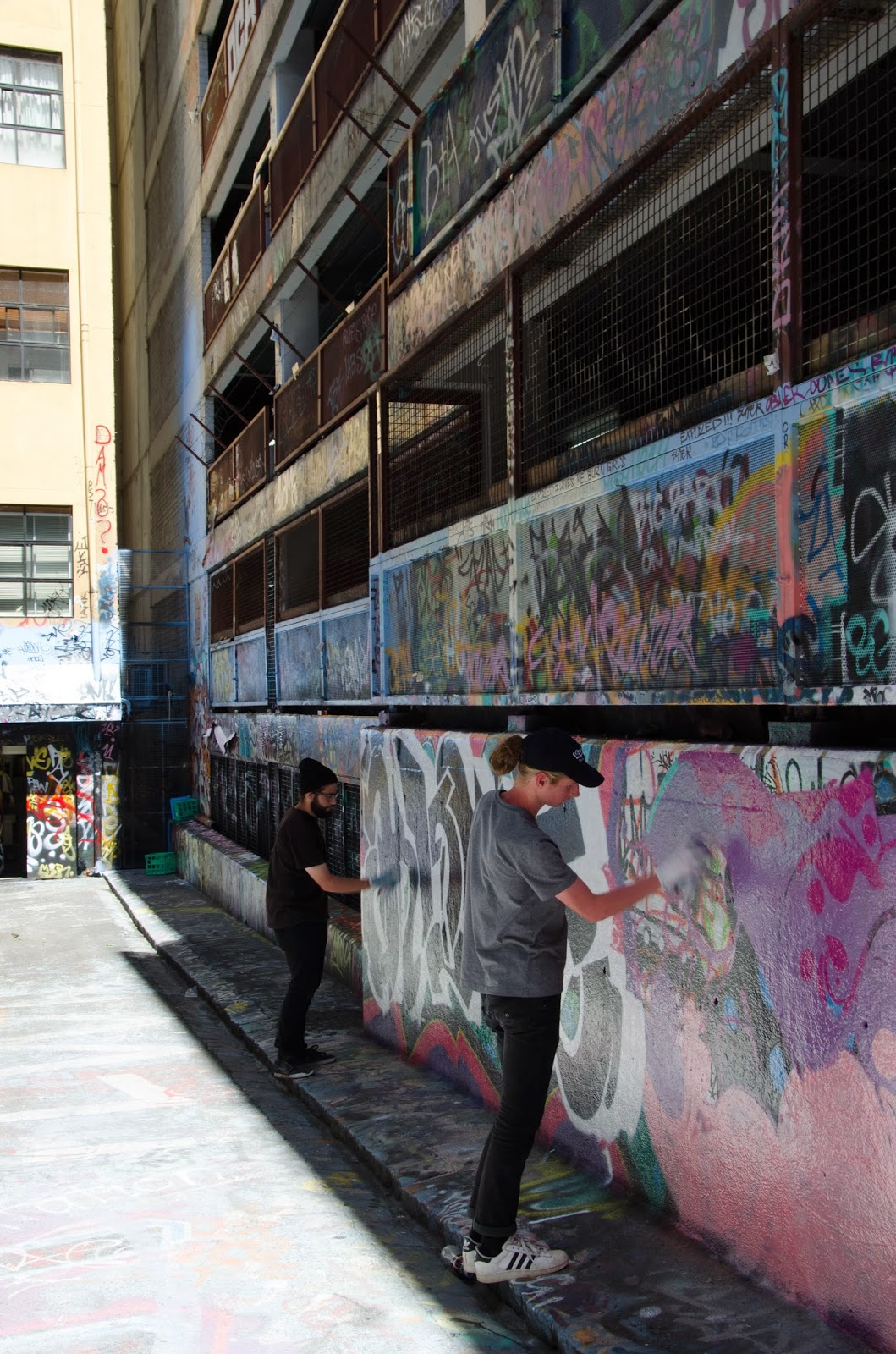 Two artists painting a wall in Caledonian Lane, Melbourne.