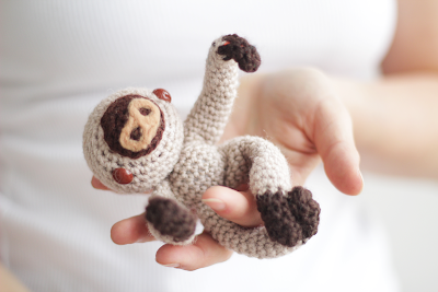 Amigurum baby sloth hanging from a finger