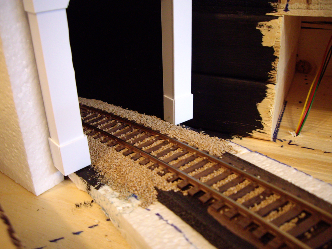 A ballasted model railroad track leading into a styrene tunnel portal