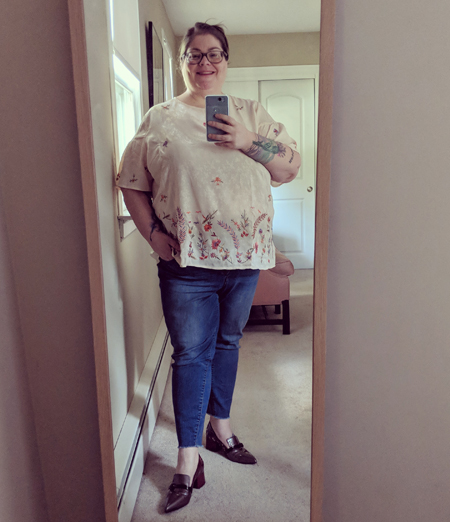 image of me in a full-length mirror wearing a pink top with embroidered flowers, blue jeans, and grey and burgundy pumps, with my hair pulled back and glasses on