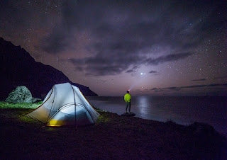 Camper standing near tent,staring at the glorious stars