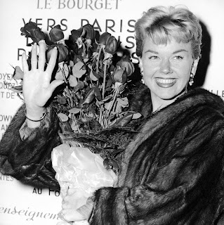 Doris Day segura um buquê no aeroporto Le Bourget em Paris, França, em foto de 1955 — Foto: Associated Press