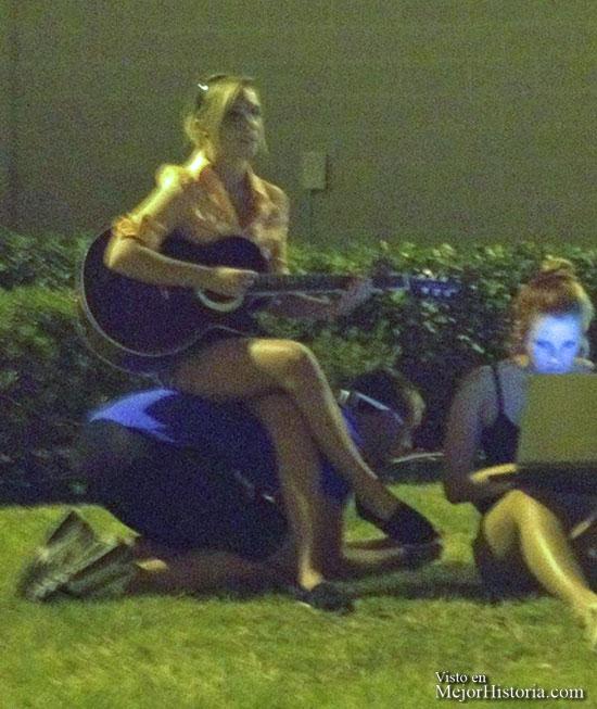 Chico se ofrece como asiento para que chica toque la guitarra en un grupo de amigos.