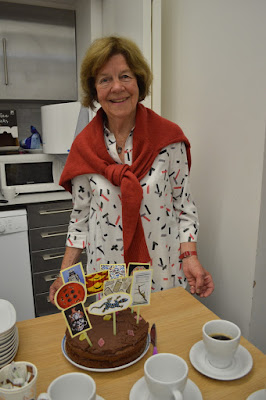 Lady stands in front of chocolate cake smiling