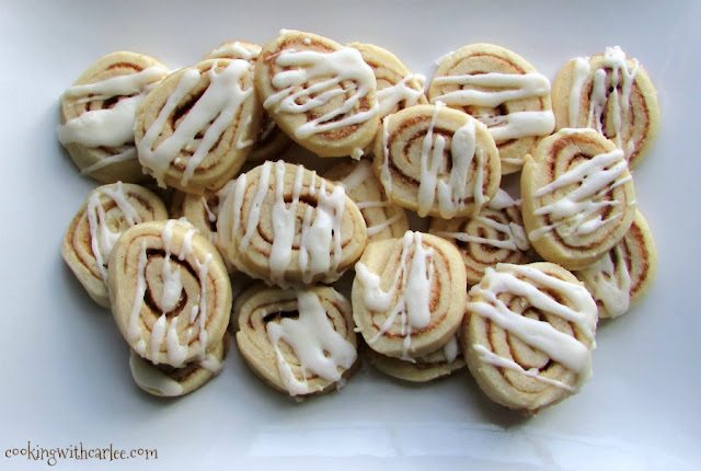 pile of cinnamon roll cookies with drizzle of cream cheese glaze