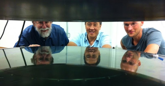 UC Santa Cruz researchers worked with Structured Materials Industries to design and build an atomic layer deposition (ALD) system large enough to accommodate telescope mirrors. Andrew Phillips, Nobuhiko Kobayashi, and David Fryauf (l to r) examined the deposition chamber. (Photos by T. Stephens)