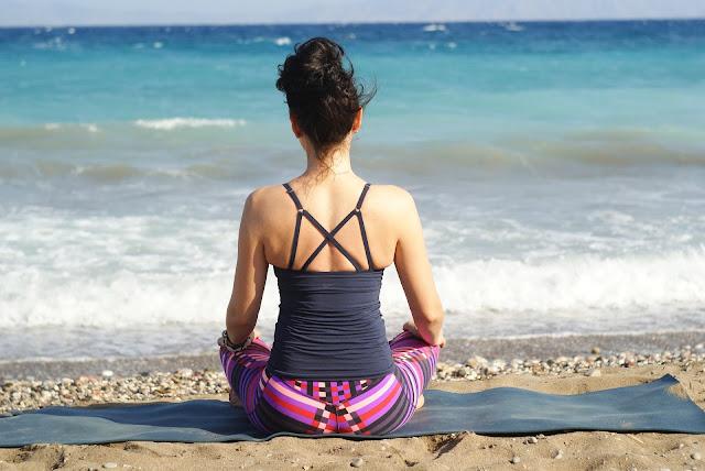 woman on beach doing self care meditation