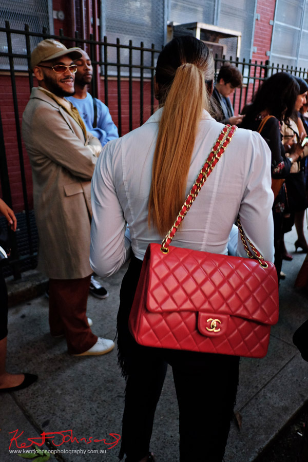 Woman with pony tail, white fitted shirt, large red channel shoulder bag. Street Fashion Sydney - New York Edition photographed by Kent Johnson