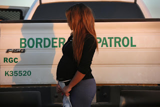 A pregnant immigrant from El Salvador stands next to a U.S. Border Patrol truck after turning herself in to border agents.  Getty Images