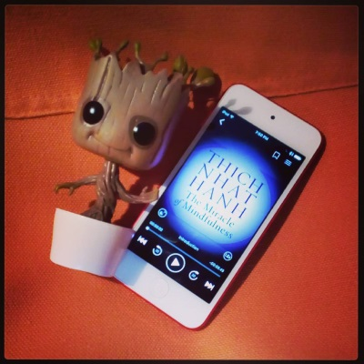 A large-headed bobblehead of Baby Groot, a tree-person in a small white pot, appears against an orange canvas background beside a white iPod with The Miracle of Mindfulness's purple, text-centric cover on its screen.
