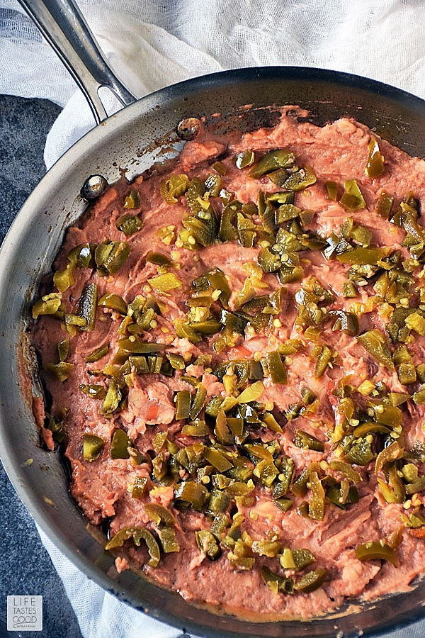 Refried beans spread to cover skillet and topped with diced jalapenos