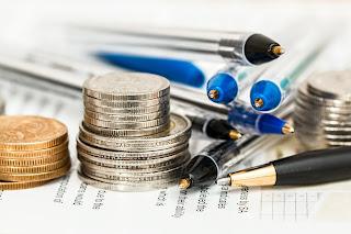 monedas, documentos y bolígrafos