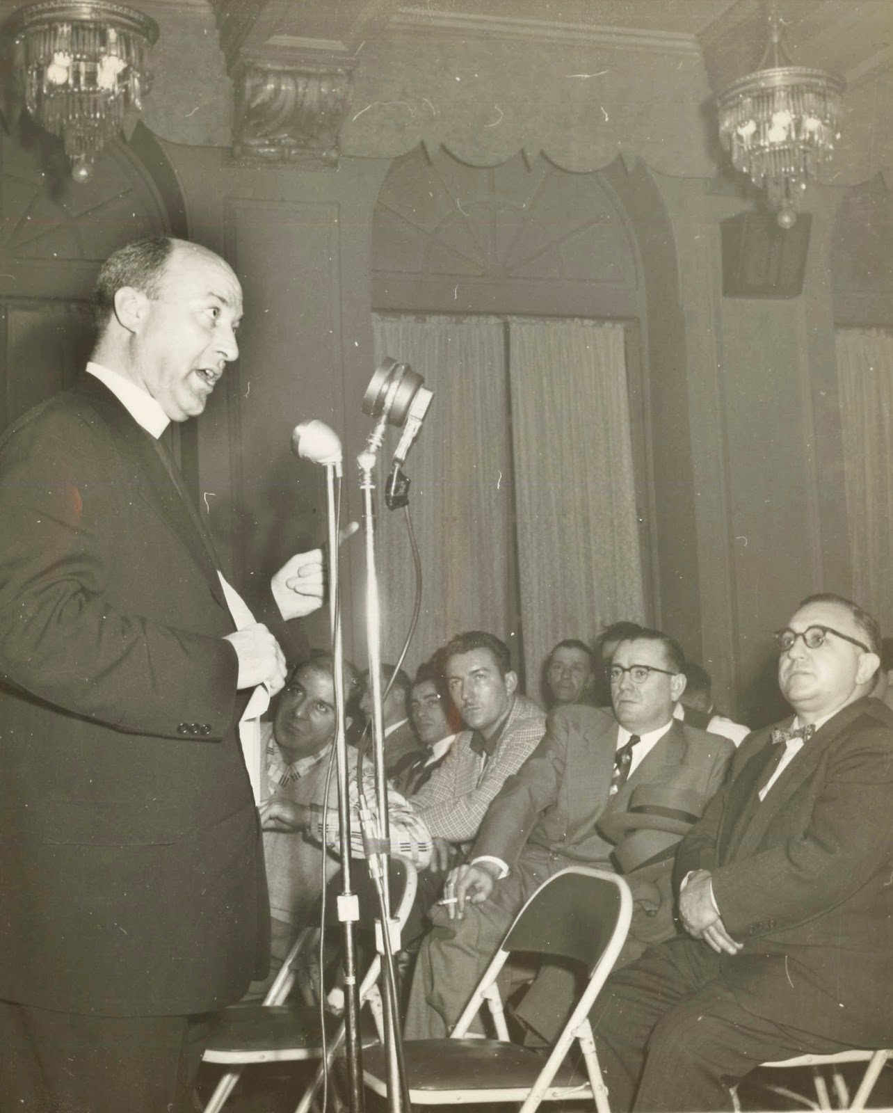 A black and white photograph of a man in a priest's collar speaking into a microphone in front of a crowd of seated men in suits.