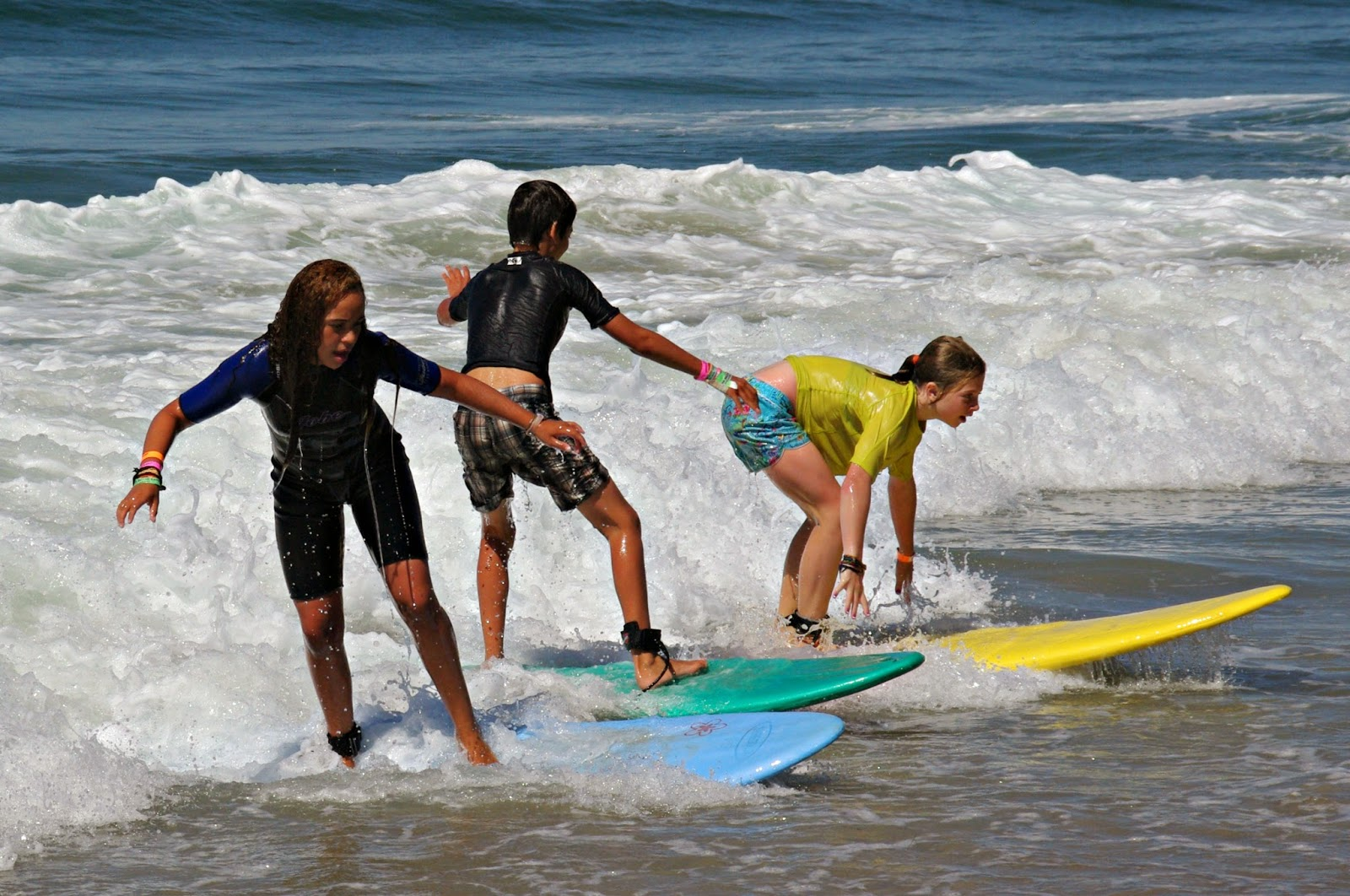 Three campers learning to surf at Aloha Beach Camp's Los Angeles Summer Camp for kids and teens in L.A.