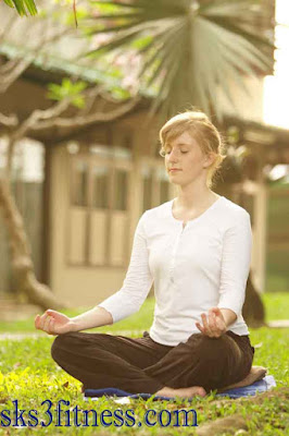 A girl meditating in Aakash mudra / hand gesture in garden on grass